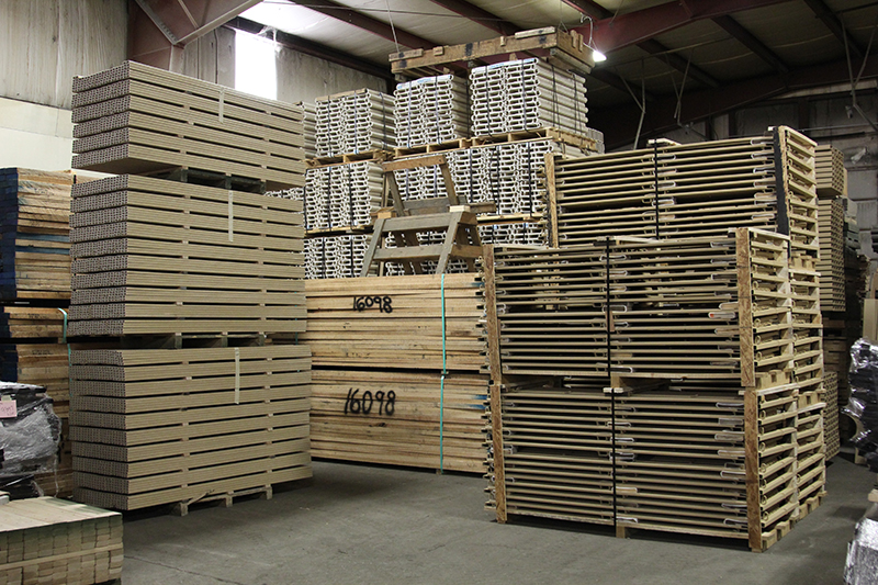 Interior of the Stephan Wood Products warehouse, full of troop carrier seats in stacks, along with other FRP and composite material.