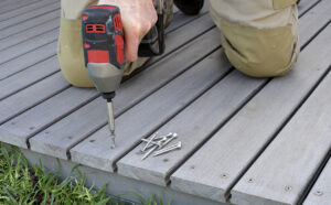 Composite decking vs wood, how does Stephan Wood Products handle this issue? A man installing a composite deck, drill in hand.