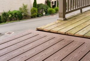 Natural wood vs composite, side by side on a deck platform. The natural wood is decaying and greening.